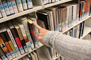 Library fingering books on a shelf