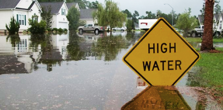 "flooded neighborhood behind ""High Water"" sign"